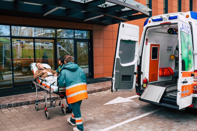 Serious and professional team of doctors in the ambulance moving on a patient into the hospital during an emergency situation.