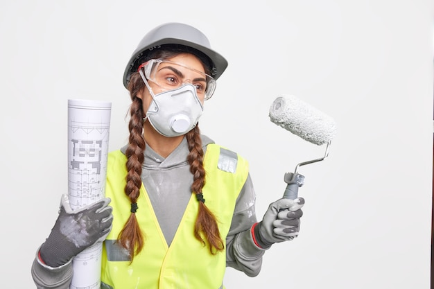 구조에 대한 자세한 계획을 작성하고 건설을 개발하는 심각한 전문 여성 건축가는 보호 얼굴 마스크 헬멧 장갑을 착용하고 청사진 페인트 롤러를 보유합니다.