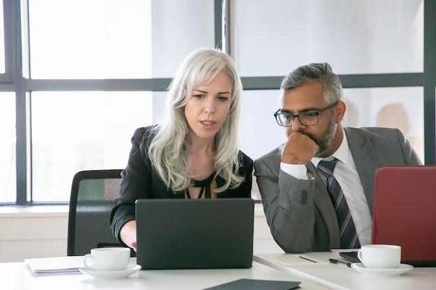 Responsabile di progetto serio che mostra la presentazione sul computer portatile al collega o al capo in ufficio. colpo medio, vista frontale. concetto di lavoro di squadra e comunicazione