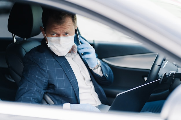 Serious prosperous entrepreneur poses in own transport, has telephone conversation, uses modern technologies to be always in touch, wears medical mask and gloves during quarantine and pandemic