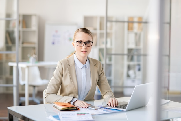 Serious puzzled attractive young businesswoman in beige jacket and blouse sitting at table in office and doing paperwork