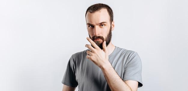 Серьезно озадаченный красивый мужчина-модель с бородой, держащий руку за подбородок, как будто думает о чем-то, с подозрением прищуривается в камеру и стоит на сером фоне. мужчина решает, что купить