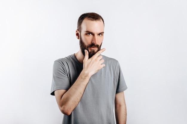 何かを考えているかのようにあごに手を握り、不審な表情でカメラに目を細め、灰色の表面の上に立っているひげを持つ深刻な困惑したハンサムな男性モデル