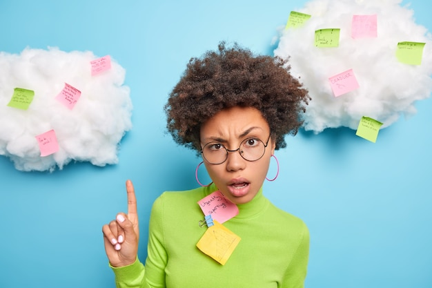 Serious puzzled woman points index finger above raises eyebrows surrounded with sticky notes writes down reminding notes tasks what to do wears round spectacles