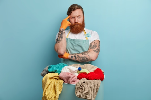Serious red haired man householder ponders on something, keeps finger on temple, poses near basin full of laundry and washer, listens washing instructions from wife, wears apron. housework concept