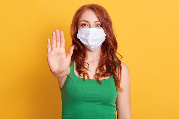 Serious redhaired woman makes stop gesture, pulls palm towards camera, wears medical flu mask and green shirt, stay at home not to spread coronavirus disease.