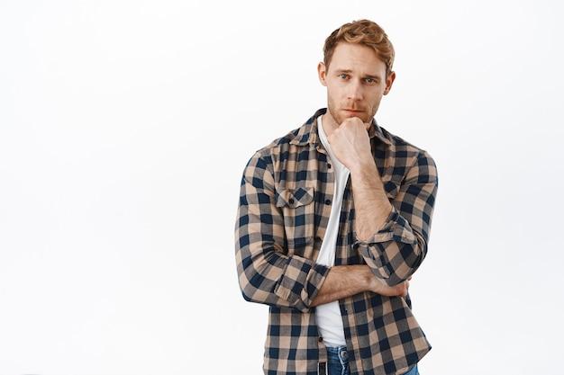 Серьезный рыжий взрослый мужчина выглядит задумчивым, трогает подбородок и размышляет, делает выбор, решение, стоя над белой стеной