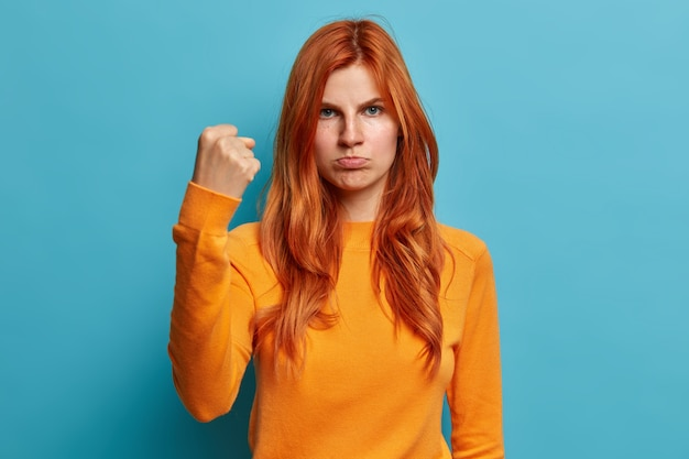 Serious redhead european woman looks angrily shows fist asks not to bother her purses lips and has irritated face expression dressed in casual orange jumper.