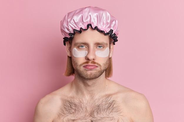강모와 콧수염을 가진 심각한 빨간 머리 남자는 눈 아래 목욕 모자 미용 패치를 착용하고 실내에서 잠자는 후 붓기를 피하려고합니다.