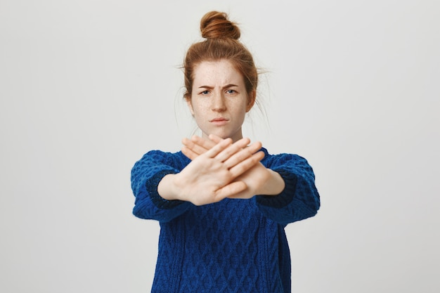 Serious redhead woman extend hand to show stop, restrict or prohibit