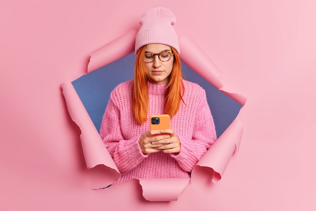 Serious redhead woman holds mobile phone and chats with friends in social networks reads news in email wears pink hat and knitted sweater connected to wireless internet breaks through paper wall