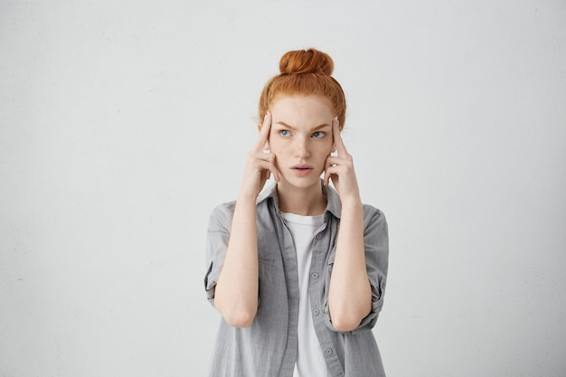 Serious redhead young caucasian woman holding fingers on her temples and looking up sideways with concentrated and focused expression, as if trying to remember something important