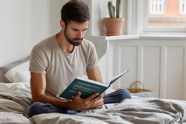 Серьезный расслабленный небритый мужчина держит книгу перед лицом, одетый в повседневную футболку, сидит в позе лотоса на кровати
