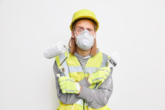 Serious repairman wears protective face mask helmet and gloves crosses arms holds paint roller brush tired of daily routines at construction works on house renovation. man builder with equipment