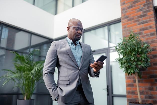 真面目な金持ちの実業家。スマートフォンでメールを読んでスタイリッシュなスーツを着て真面目な金持ちの実業家