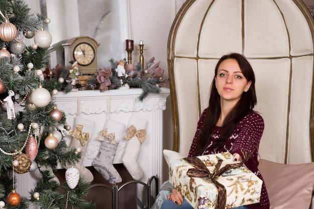 カメラを見ながら、クリスマスツリーの近くにプレゼントサインを与えるエレガントな大きな椅子に座っている深刻な金持ちの若い女性