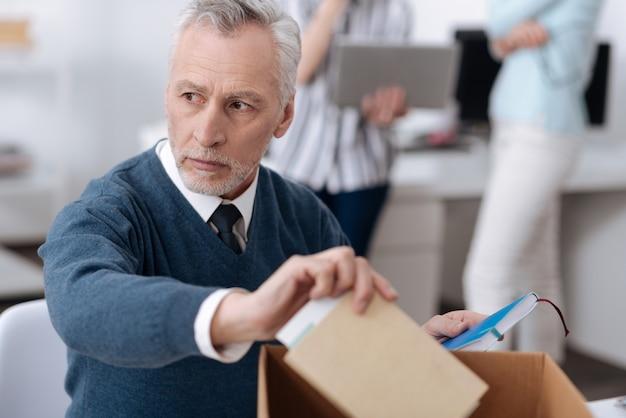 脇を見ながら箱からノートを取っている青いカーディガンを身に着けている深刻な悲しいひげを生やした男性