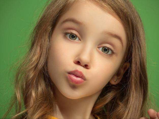 Serious, sad, doubtful, thoughtful teen girl standing at green studio