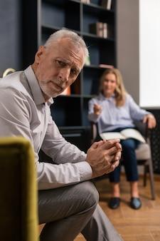 彼の指が彼の前にぼんやりと見ながら屋内に座って交差した深刻な悲しい白髪の男