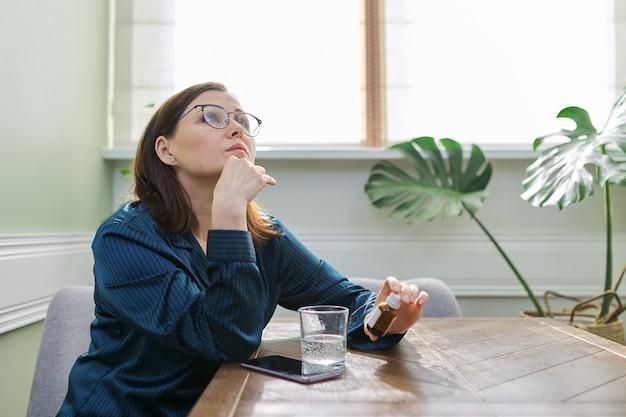 의학, 물 유리, 전화 심각한 슬픈 성숙한 여자. 테이블에 집에 앉아 진정 방울을 마시는 잠옷 여성. 신체 심리적 정신 건강 중년, 복사 공간