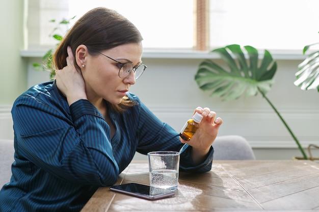 薬、コップ一杯の水、電話で深刻な悲しい成熟した女性。鎮静剤の滴を飲んで、テーブルで家に座っているパジャマの女性。身体心理メンタルヘルス中年、コピースペース
