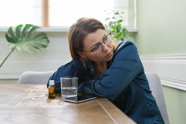 薬、コップ一杯の水、電話で深刻な悲しい成熟した女性