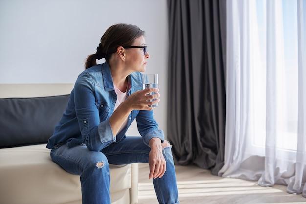 집에 앉아 창밖을 내다보며 물 한 잔을 들고 있는 심각한 슬픈 중년 여성. 건강 문제, 정신 장애, 우울증, 갱년기 및 개인 문제