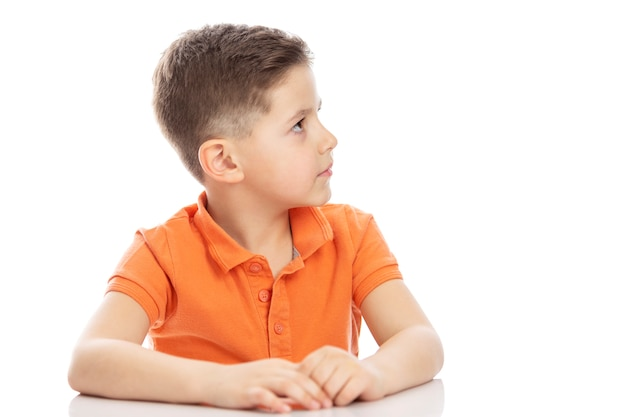 A serious school-age boy in a bright orange polo t-shirt sits at a table and looks to the side. isolirvoan on a white background.