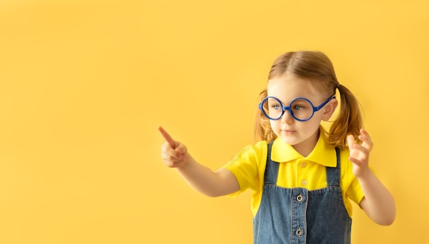 Serious school child in glasses isolated yellow background looking at copy space and finger pointing to place for text. back to school