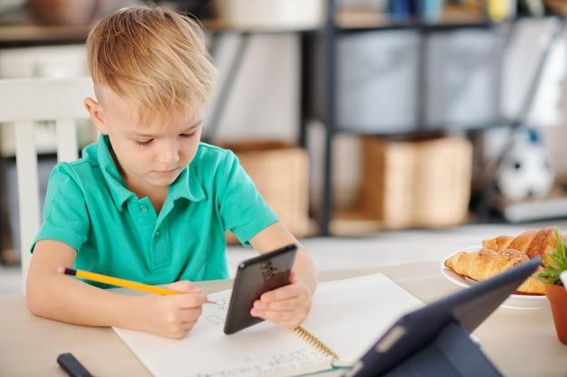Серьезный школьник проверяет информацию на смартфоне при решении математических уравнений за партой
