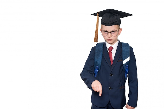 Serious schoolboy in a suit, glasses and an academic hat is pointing down
