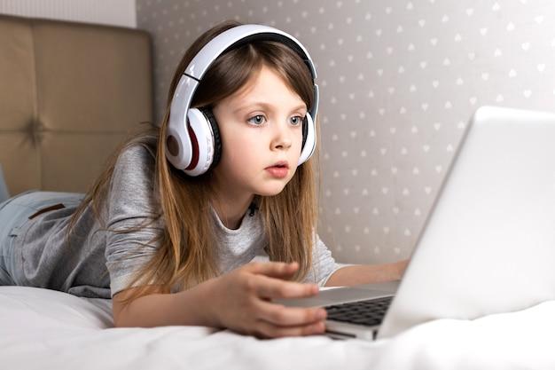 Serious schoolgirl in headphones using laptop at home