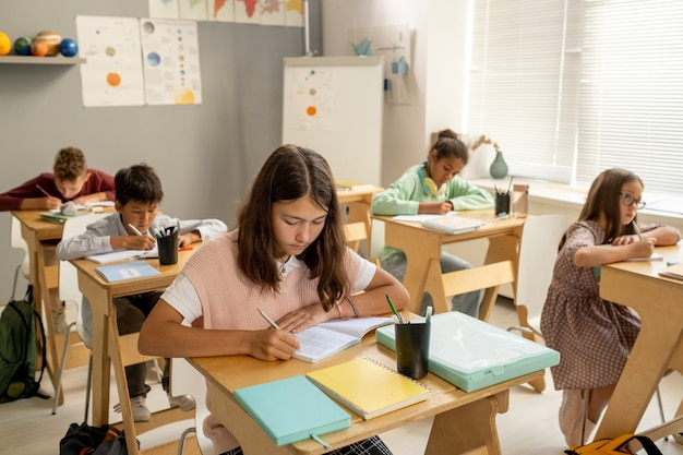 Serious schoolgirl and her intercultural classmates making notes in copybooks