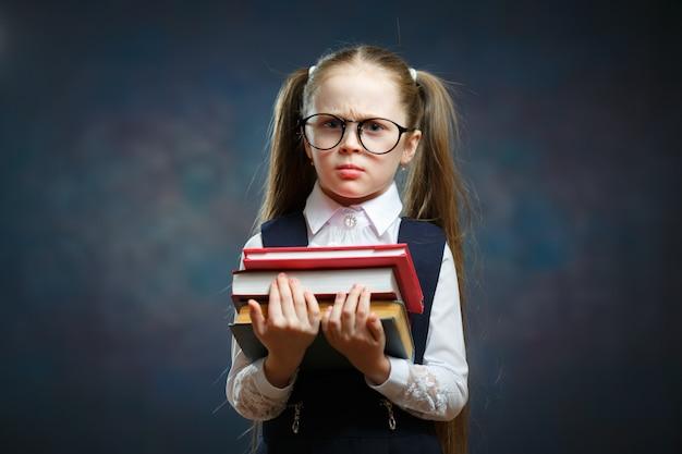 深刻な女子高生のメガネをかけて本の山を保持