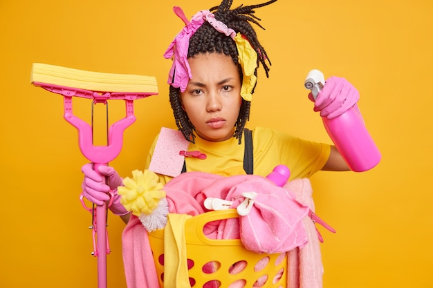 Serious scrupulous afro american housewife has dreadlocks holds with cleaning accessories