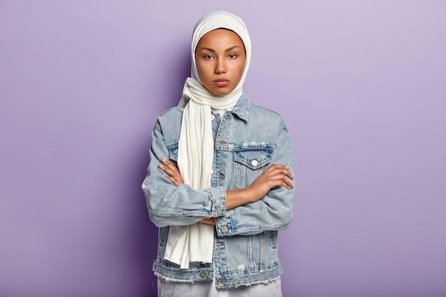 真面目な自信のあるアラビアの女性は、手を胸に交差させ続け、暗い健康な肌をしています