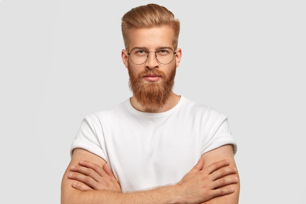 Serious self assured man architect keeps hands crossed, has ginger thick beard and mustache