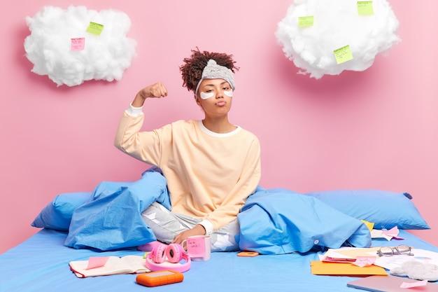 真面目な自信のあるアフリカ系アメリカ人のミレニアル世代の女の子が腕を上げ、上腕二頭筋が誇りに思っていることを示しています
