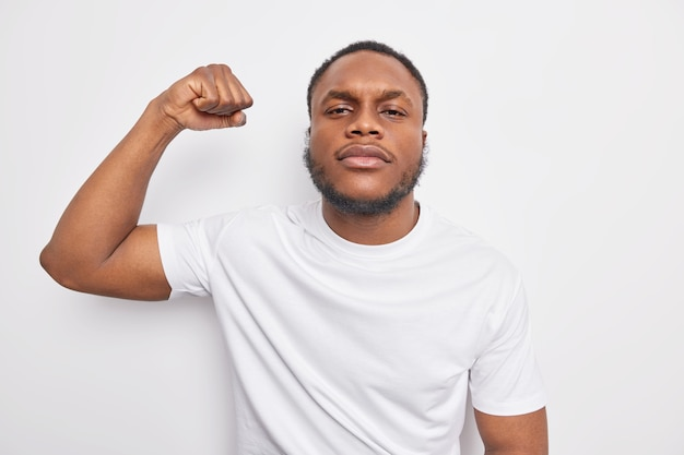 Serious self confident black man with beard raises arm shows muscles being assured feels strong and powerful