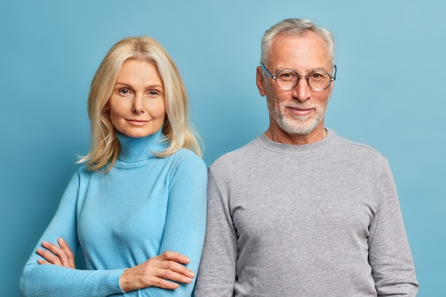 Serious self confident blonde pretty woman stands with arms folded near her husband pose for making common photo dressed in casual turtlenecks isolated over blue wall