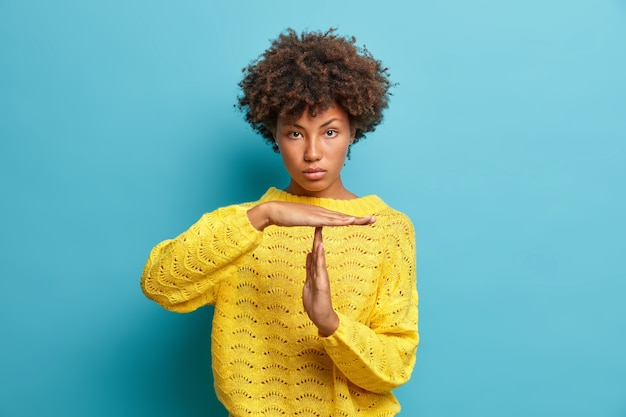 Serious self confident curly haired woman makes timeout gesture demonstrates limit asks to stop dressed in yellow knitted jumper isolated on blue wall