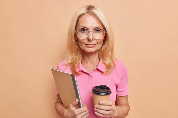 자신감 넘치는 여성 직원은 커피를 마시며 공책을 들고 큰 투명 안경을 쓰고 분홍색 티셔츠를 갈색 벽에 기대고 있다