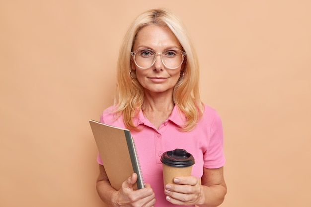 Serious self confident female worker has coffee break holds notebooks wears big transparent glasses and pink t shirt poses against brown wall