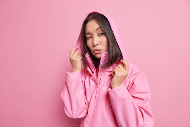 黒髪の真面目な自信に満ちたミレニアル世代の女の子は、頭にアノラックのフードをかぶっており、寒い風の強い日に散歩するピンクの壁をモデルにしています。人とスタイル