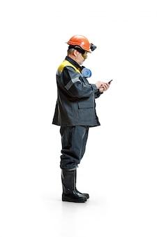 Minatore maschio barbuto senior serio che sta alla macchina fotografica con lo smartphone su un bianco