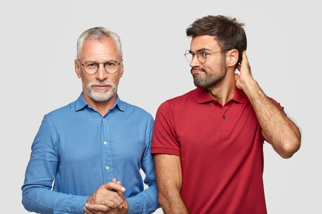Serious senior bearded man in blue elegant shirt have talk with son who looks at him with puzzlement