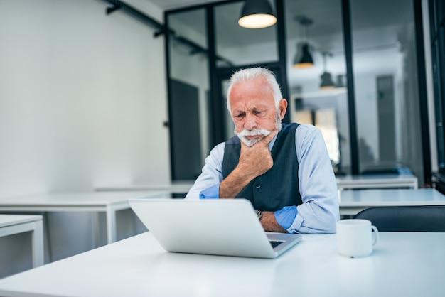Serious senior business man looking at laptop.