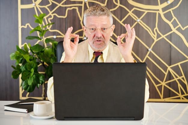 Серьезный старший бизнесмен видео звонит своему деловому партнеру или коллеге, чтобы обсудить детали проекта
