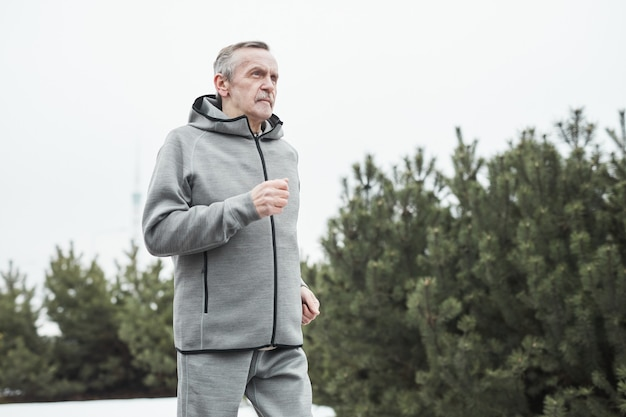 森の中を一人で走りながら腕を振る灰色のスポーツスーツの真面目な白人男性