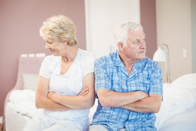 Serious senior couple sitting on bed at home